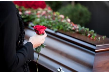Mourning woman holds rose at funeral
