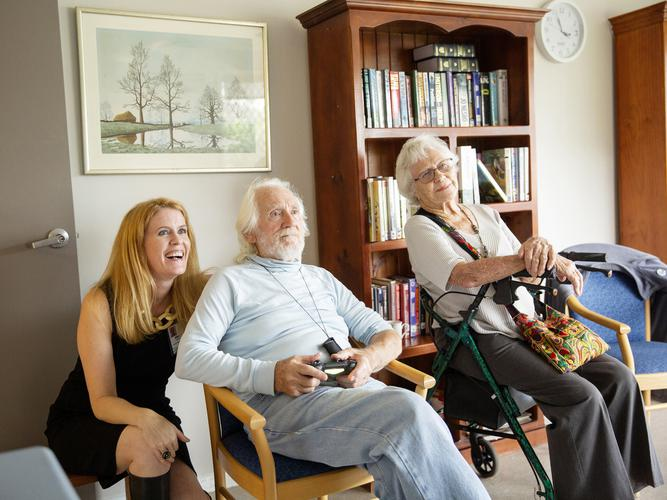 Psychology and Behavioural Science Researcher from the University of England, Alex McCord, with Feros Village residents, Hugh Webster and Lois Sanderson, playing video games. [Source: Feros Care]