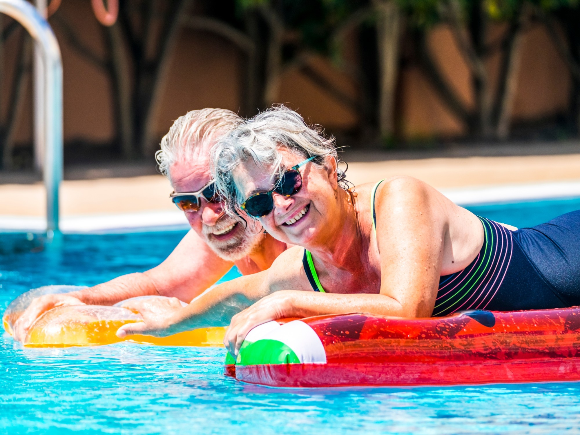 Couple relaxing in their retirement village pool