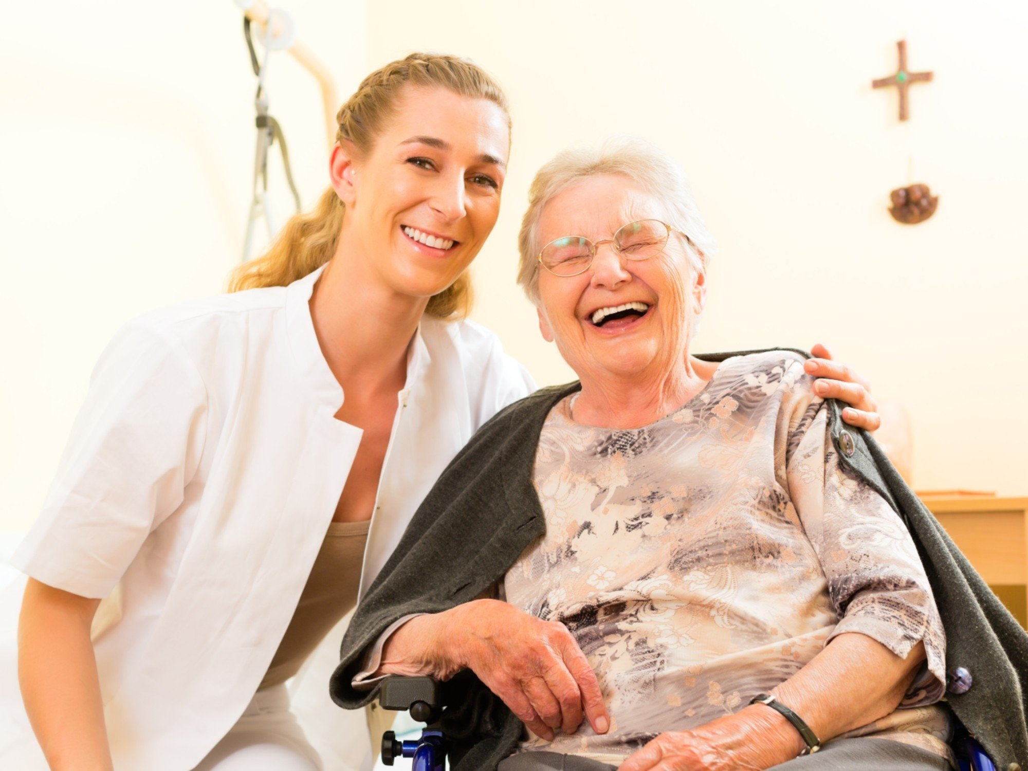 An older person receiving help from a carer at home